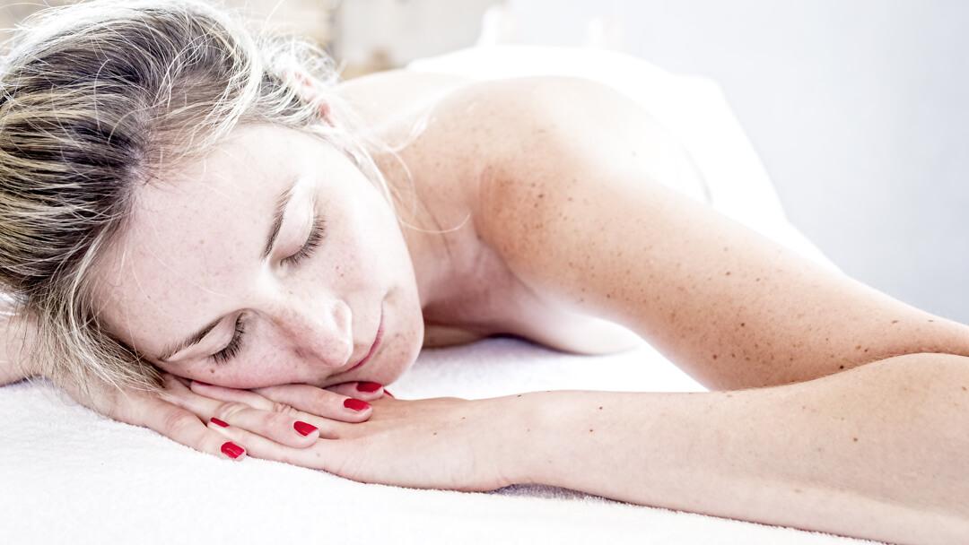 entspannte Dame mit rot lackierten Fingernägeln nach einer Massagen