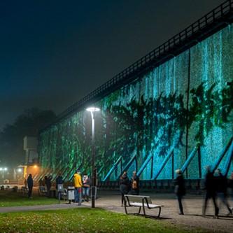 Besucher vor dem alten Gradierwerk mit Impressionen der lichtsicht 7 Triennale.